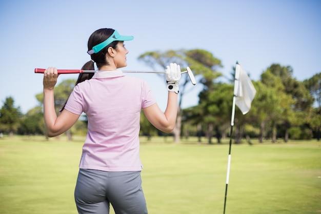 Rückansicht der frau, die golfschläger hält