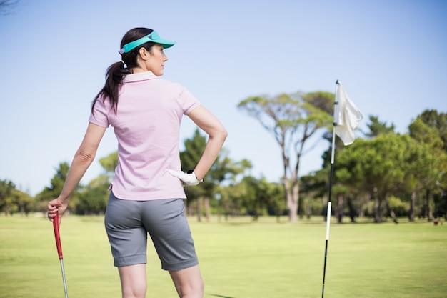 Rückansicht der frau, die golfschläger mit hand auf hüfte hält