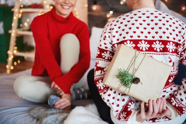 Rückansicht der frau, die ihrem freund weihnachtsgeschenk gibt