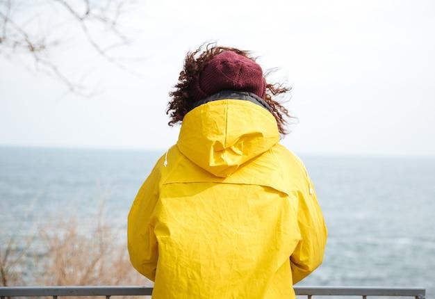 Rückansicht der frau, die weg im meer im gelben regenmantel schaut