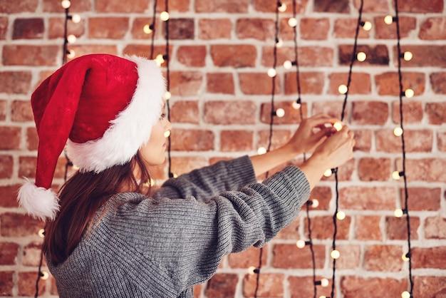 Rückansicht der frau, die weihnachtsbeleuchtung prüft