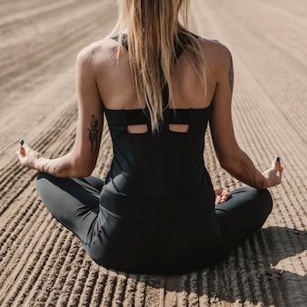 Rückansicht der frau, die yoga am strand tut
