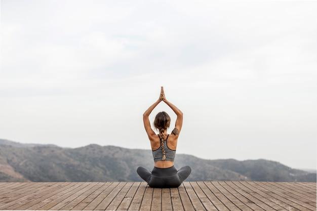 Rückansicht der frau, die yoga im freien tut