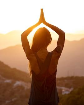 Rückansicht der frau, die yoga im sonnenuntergang tut
