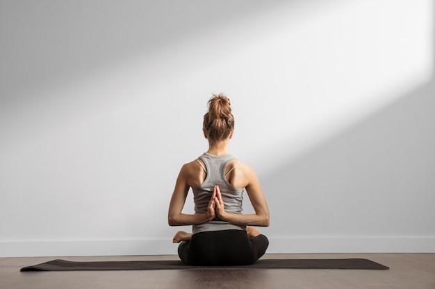 Rückansicht der frau, die yoga tut