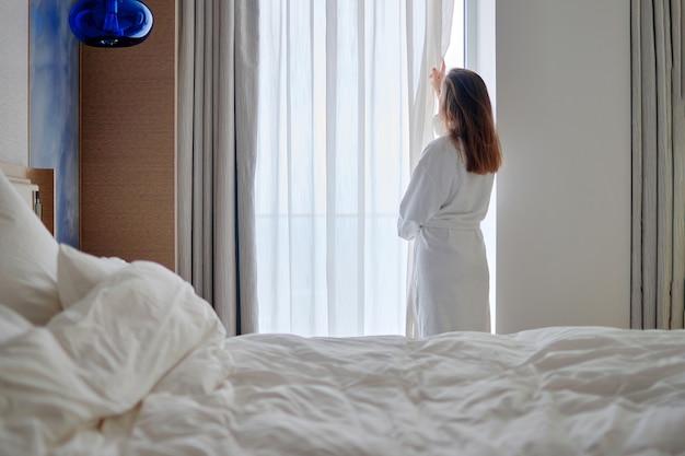 Rückansicht der frau im bademantel aufwachen, vorhänge öffnen und guten morgen genießen, während sie sich im gemütlichen komfortschlafzimmer im hotelzimmer entspannen.