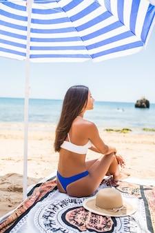 Rückansicht der frau mit gebräunter haut, die am strand im sonnigen tag aufwirft. porträt von der rückseite des stilvollen mädchens im blauen bikini, der unter regenschirmen auf seehintergrund sitzt.