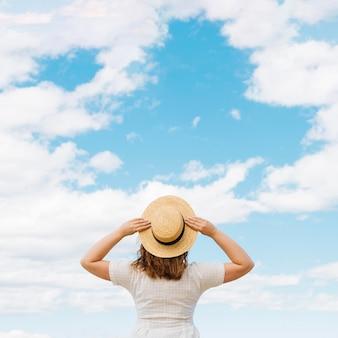 Rückansicht der frau mit hut, der wolken am himmel bewundert