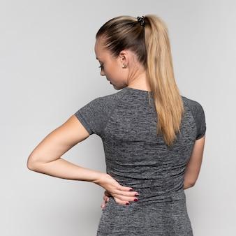 Rückansicht der frau mit rückenschmerzen