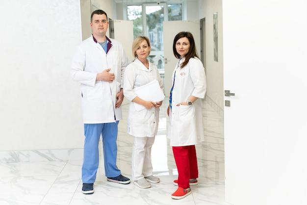 Rückansicht der frauen und männer, ärzte. mediziner stehen in der halle und schauen in die kamera. ärzte und krankenschwestern im gesundheitswesen bei der arbeit im krankenhaus. konzept des klinikteams