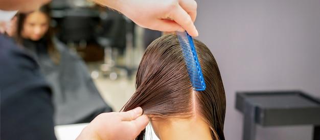 Rückansicht der friseurhände, die langes haar der jungen frau im friseursalon trennen