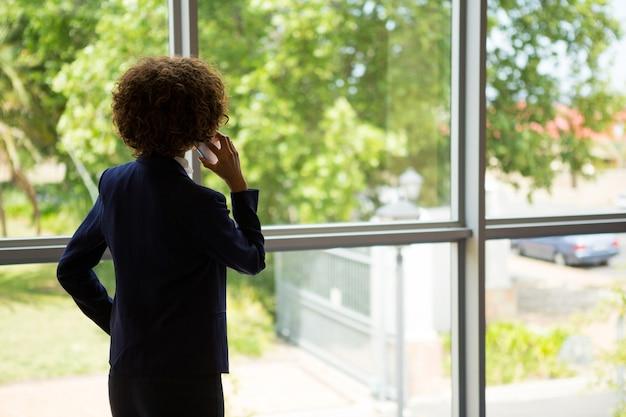 Rückansicht der geschäftsfrau, die am mobiltelefon am konferenzzentrum spricht
