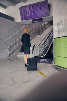 Rückansicht der geschäftsfrau, die eine trolley-tasche trägt, während sie zur geschäftsreise geht