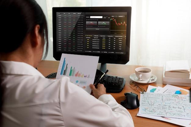 Rückansicht der geschäftsfrau, die im büro mit computer arbeitet, der diagrammberichtspapier hält und schaut. geschäftsstatistikanalyse projektstatistikdaten auf pc-bildschirm und papier. geschäfts- und finanzkonzept.