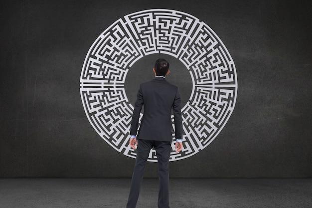Rückansicht der geschäftsmann mit einem labyrinth suchen