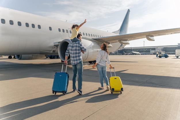 Rückansicht der glücklichen familie, die in der nähe eines großen flugzeugs mit zwei koffern im freien steht. reisekonzept