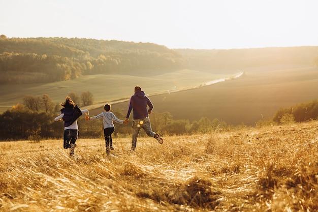 Rückansicht der glücklichen familie, die spaß auf grüner natur hat