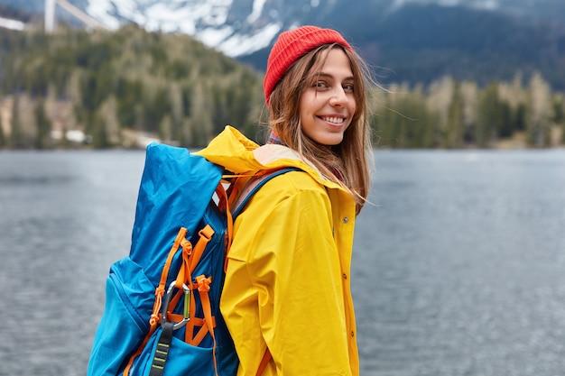 Rückansicht der glücklichen jungen europäischen frau genießt schönen ruhigen tag, naturlandschaftslandschaft, trägt rucksack