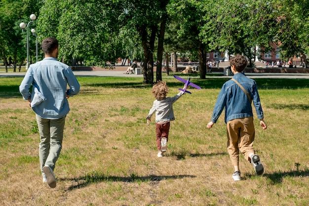Rückansicht der glücklichen jungen familie der eltern und ihres niedlichen kleinen sohnes mit spielzeug, das grünen rasen hinunter läuft, während spaß im öffentlichen park hat
