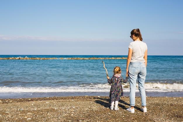 Rückansicht der glücklichen mutter und der kleinen tochter am strand
