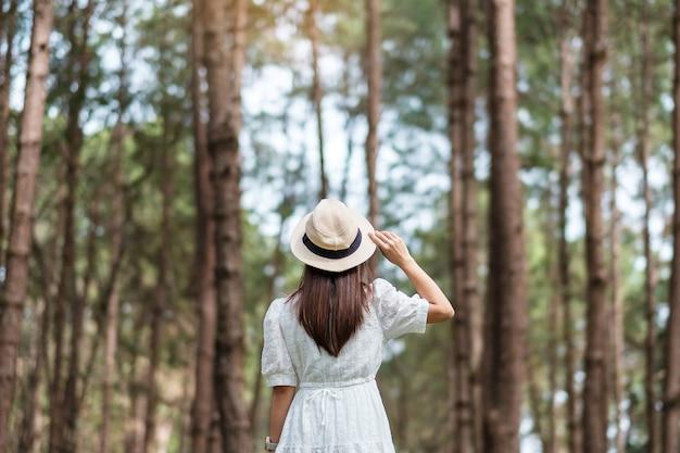 Rückansicht der glücklichen reisendenfrau, die einen verschwommenen kiefernwaldhintergrund steht und betrachtet