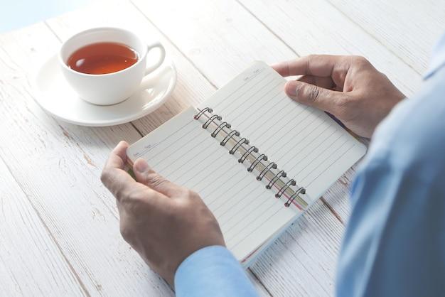 Rückansicht der hand des mannes, die eine seite eines notizblocks umblättert.