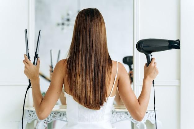 Rückansicht der hübschen jungen frau, die mit einem fön und einem haarglätter für die kamera posiert, während sie vor dem spiegel steht