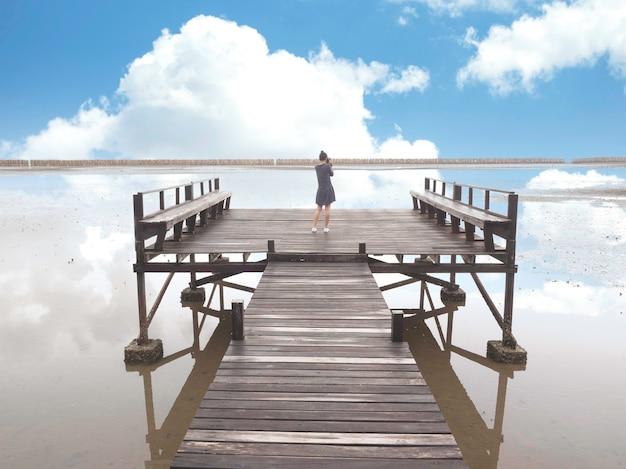 Rückansicht der jungen asiatischen frau verwenden digitalkamera, die foto der ansicht des sees mit schönem blauem himmel macht.