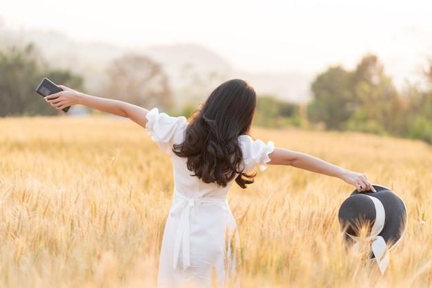 Rückansicht der jungen frau des langen haares im weißen kleid, das allein steht, streckt ihre arme aus und hält ihren hut und telefon in der goldenen farbe gerstenfeld