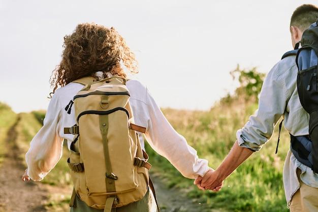 Rückansicht der jungen frau mit dem rucksack des lockigen haares, während sie ihren ehemann an der hand hält und beide landstraße entlang bewegen