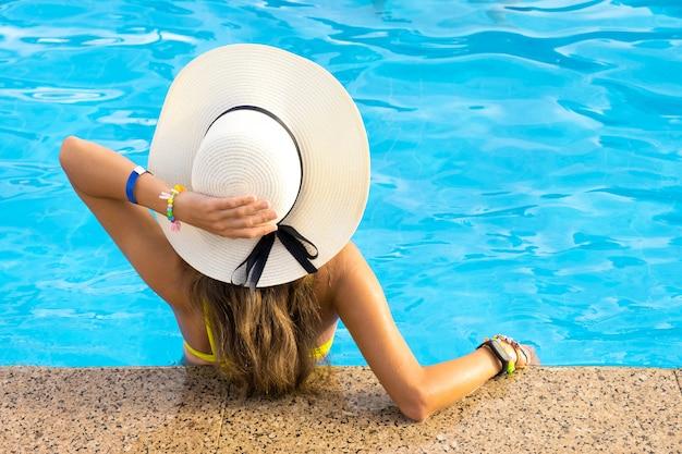 Rückansicht der jungen frau mit den langen haaren im hotelschwimmbad.
