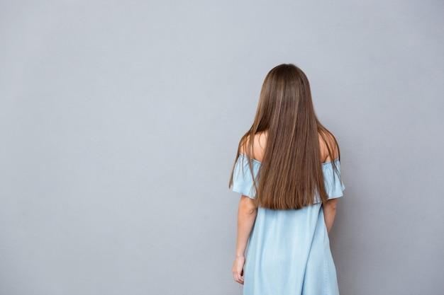 Rückansicht der jungen frau mit langen haaren im blauen kleid, die auf grauer wand steht