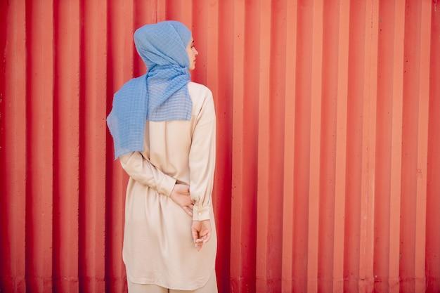 Rückansicht der jungen muslimischen frau im blauen hijab und in der hellbeigen freizeitkleidung, die durch wand stehen