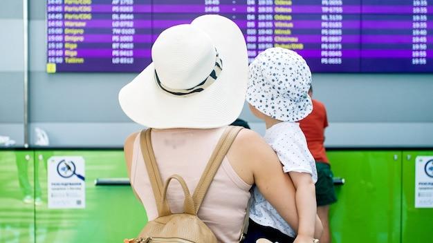 Rückansicht der jungen mutter, die ihren kleinkindsohn im flughafenterminal hält und auf die flugplananzeige schaut.