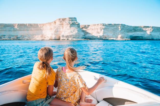 Rückansicht der kleinen niedlichen mädchen, die das segeln auf dem boot im offenen meer genießen