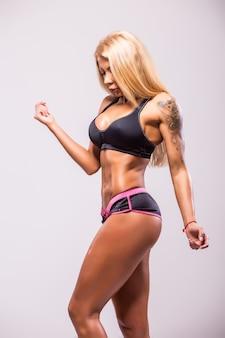 Rückansicht der lächelnden athletischen frau im bikini, die muskeln auf dunkelheit zeigt