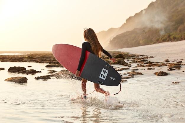 Rückansicht der laufenden frau kommt in warmes meerwasser für surfaktivitäten