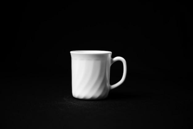 Rückansicht der leeren kaffeetasse lokalisiert auf schwarzer oberfläche