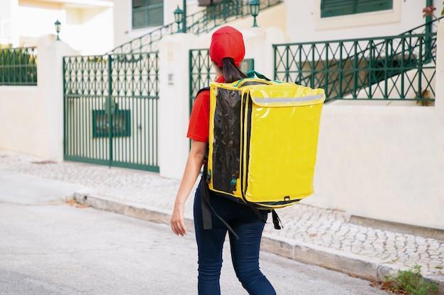 Rückansicht der lieferfrau, die gelbe thermotasche trägt. erfahrener kurier, der auf der straße im freien geht und bestellung liefert.