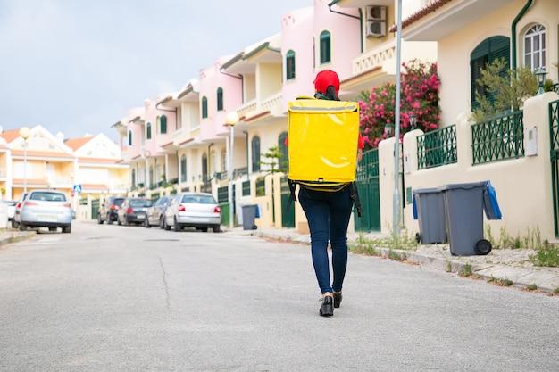 Rückansicht der lieferfrau, die gelben wärmebeutel trägt. weiblicher kurier in der roten kappe, die entlang straße geht und bestellung liefert.