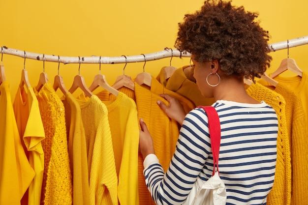 Rückansicht der lockigen dame im gestreiften pullover, trägt tasche, wählt kleidung aus, nimmt gelben pullover auf kleiderbügeln auf.