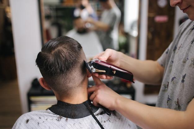 Rückansicht der männer im schönheitssalon. herrenhaarschnitt in einem friseurladen. neuer haarschnittstil 2021. professioneller friseur verwendet einen haarschneider zum fransen von haaren