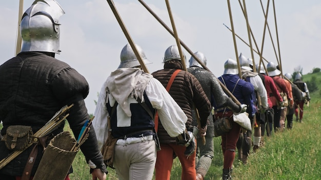 Rückansicht der mittelalterlichen gruppenritter, die auf die schlacht gehen. krieger mit speeren, schwertern, schleifen und helmen auf den köpfen. historischer wiederaufbau des 14.-15. jahrhunderts in flandern.
