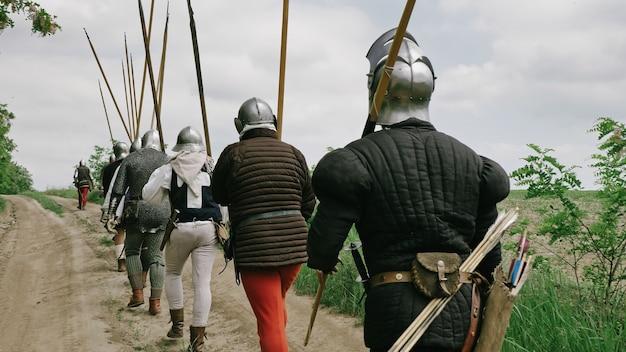 Rückansicht der mittelalterlichen gruppenritter, die auf die schlacht gehen.