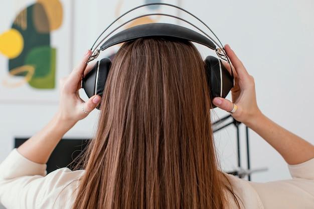 Rückansicht der musikerin, die kopfhörer aufsetzt, um lied aufzunehmen