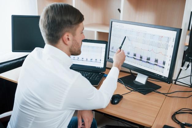 Rückansicht. der polygraph-prüfer arbeitet im büro mit der ausrüstung seines lügendetektors