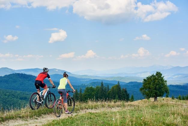 Rückansicht der radfahrer des athletenpaares, die langlaufräder auf bergpfad am sommertag radeln