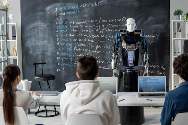 Rückansicht der reihe von schülern, die am schreibtisch vor dem automatisierungsroboter sitzen, der an der tafel anstelle des menschlichen lehrers steht