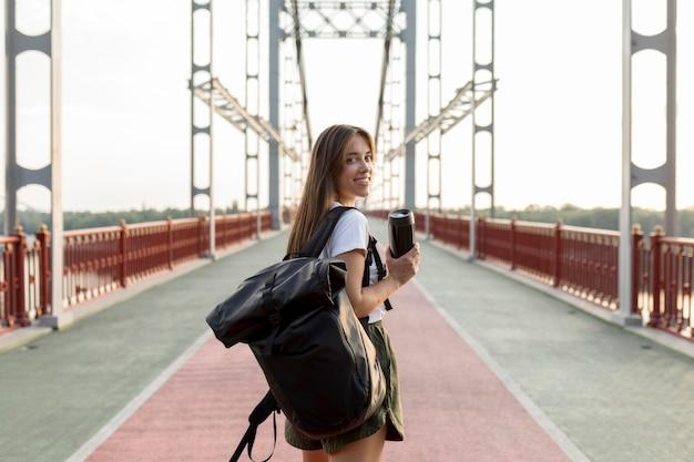 Rückansicht der reisenden frau mit rucksack, der thermosflasche während des reisens hält