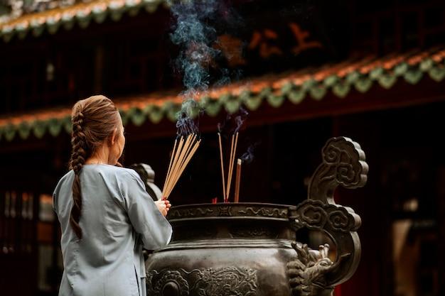 Rückansicht der religiösen frau am tempel mit brennendem weihrauch
